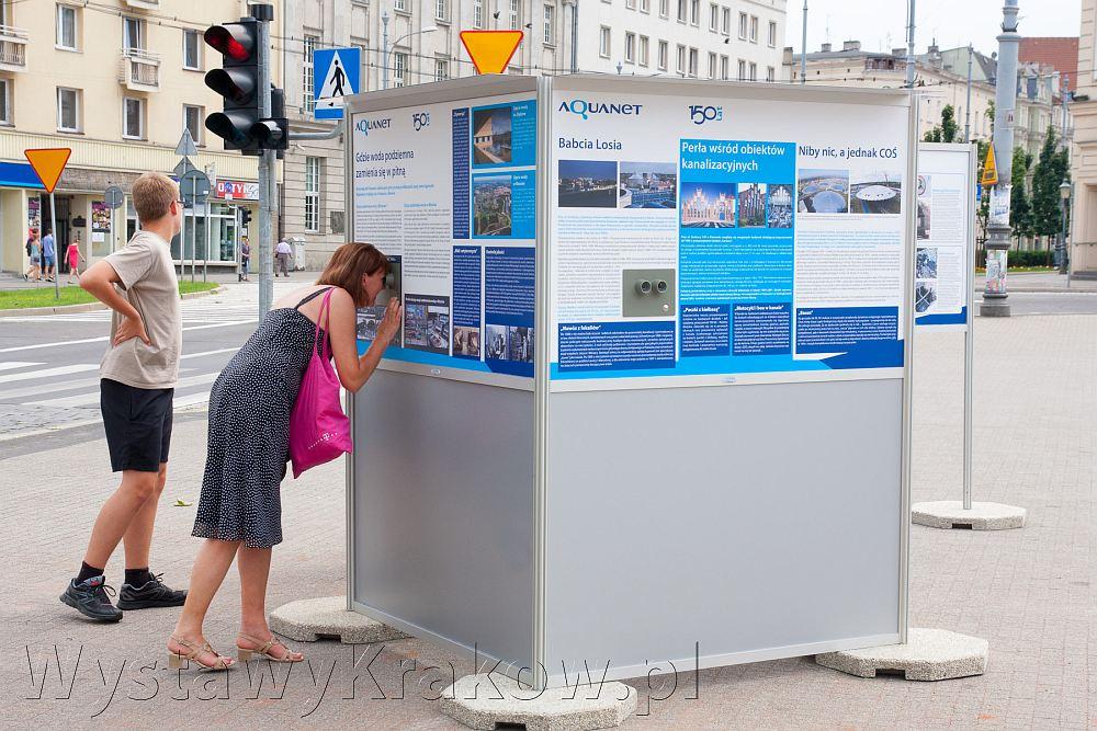 Wystawa plenerowa w Poznaniu - wystawy outdoor to świetna promocja firmy albo wydarzeń. Szczególnie wystawy 3D. Na zdjęciu kobieta zaglądająca przez wizjer fotoplastikonu.